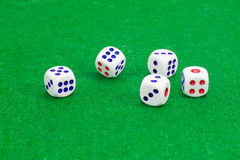 Traditional plastic six-sided dice on table with green cloth. Traditional plastic white six-sided dice with red and blue dots and rounded corners on a table Stock Photography