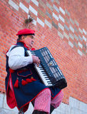 Traditional Poland busker. KRAKOW, POLAND - NOV 11, 2014: Street musician wore in traditional Poland dress playing on the street of Krakow Royalty Free Stock Photo