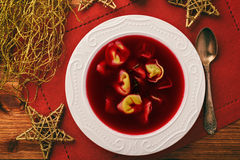 Traditional Polish christmas soup -  red borscht soup with dumplings on white plate. Royalty Free Stock Photo