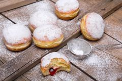Traditional Polish donuts on wooden background. Tasty doughnuts with jam Royalty Free Stock Photo