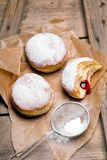 Traditional Polish donuts on wooden background. Tasty doughnuts with jam Stock Photos