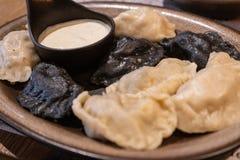 Traditional polish dumplings perogi served on a plate. Accompanied with a white garlic sauce stock photo