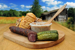 Traditional Polish food. Bread, smoked cheese, kielbasa and other traditional food served outside in the countryside royalty free stock image
