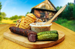 Traditional Polish food. Bread, smoked cheese, kielbasa and other traditional food served outside a country cottage stock photo