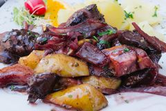 Traditional Polish Food in Gdansk. Traditional Polish food in a restaurant in Gdansk, Poland. Potatoes with liver and fruit royalty free stock images
