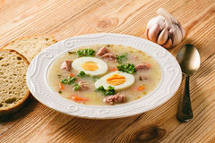 Traditional polish white borscht - zurek, sour soup with white sausages and eggs. Stock Photo