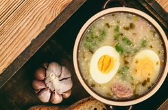Traditional polish white borscht - zurek, sour soup with white sausages and eggs. Royalty Free Stock Images