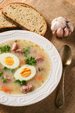 Traditional polish white borscht - zurek, sour soup with white sausages and eggs. Stock Image