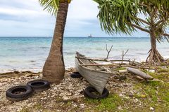 Traditional Polynesian outrigger canoe lies atop of old tires on rocky shore of Funafuti atoll lagoon, Tuvalu, Polynesia, Oceania. stock image