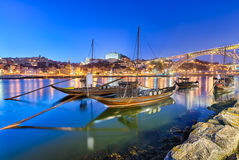 Traditional port wine transport boats in Porto, Portugal. Traditional boats on the Douro river in Porto, Portugal with the Dom Luiz bridge in the background stock photo