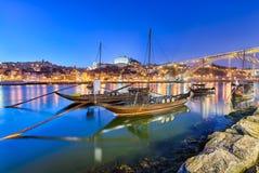 Traditional port wine transport boats in Porto, Po. Traditional boats on the Douro river in Porto, Portugal with the Dom Luiz bridge in the background Stock Photo
