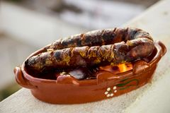 Traditional portuguese chourico or spanish chorizo prepared in a. Special clay pot on alcohol Stock Photos