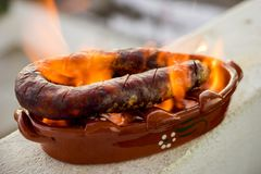 Traditional portuguese chourico or spanish chorizo prepared in a. Special clay pot on alcohol Stock Photography
