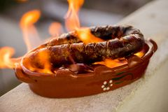 Traditional portuguese chourico or spanish chorizo prepared in a. Special clay pot on alcohol Royalty Free Stock Images