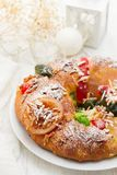 Traditional portuguese Chrismas cake Bolo rei. On white dish on wooden background Royalty Free Stock Image