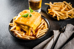 Traditional Portuguese food, francesinha. Traditional Portuguese snack food. Francesinha sandwich of bread, cheese, pork, ham, sausages, with tomato beer sauce stock images