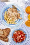 Turkey steak with french fries and tomato salad royalty free stock image