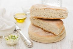 Traditional portuguese potato bread of Madeira - bolo de caco. On white wooden background royalty free stock photo