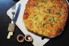 Traditional potato pie for  family dinner, baked until Golden brown in the oven, on  dark background closeup. A Traditional potato pie for a family dinner Royalty Free Stock Photography
