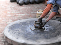 Traditional pottery craftsmanship. Hands of a potter crafting traditional style pottery. This photo can be used to demonstrate how pottery is done in the old Royalty Free Stock Image