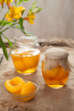 Traditional preserved peaches compote with juice in glass jars Royalty Free Stock Images