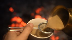 Traditional process boil Turkish coffee on coals. Boil Turkish coffee on coals. In the frame: Pour out the turkey ready coffee into the cup. This is a stock footage