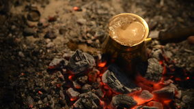Traditional process boil Turkish coffee on coals. Boil Turkish coffee on coals. In this video: Coffee in Turkish boils. Added light to light the tank. This is a stock footage