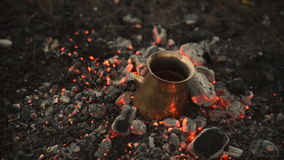 Traditional process boil Turkish coffee on coals. Boil Turkish coffee on coals. In this video: Coal is mixed around the tank. This is a traditional recipe for stock video