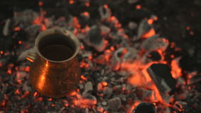 Traditional process boil Turkish coffee on coals. Boil Turkish coffee on coals. In this video: Coal is mixed around the tank. This is a traditional recipe for stock footage