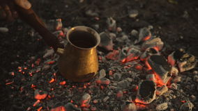 Traditional process boil Turkish coffee on coals. Boil Turkish coffee on coals. In this video: Coal is mixed around the tank. This is a traditional recipe for stock video footage