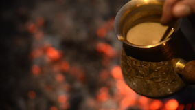 Traditional process boil Turkish coffee on coals. Boil Turkish coffee on coals. In this video: In a jar mix coffee with a spoon against the background of stock video footage