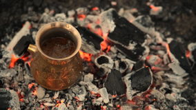 Traditional process boil Turkish coffee on coals. Boil Turkish coffee on coals. In this video: Milk is poured into the Turk. This is a traditional recipe for stock video