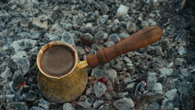 Traditional process boil Turkish coffee on coals. Boil Turkish coffee on coals. In this video: Coffee is mixed in a Turk. This is a traditional recipe for stock footage