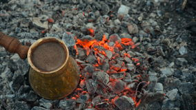 Traditional process boil Turkish coffee on coals. Boil Turkish coffee on coals. In this video: Coffee is mixed in a Turk. This is a traditional recipe for stock video footage