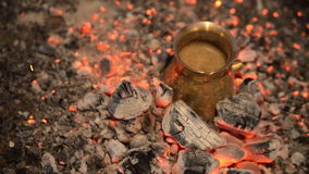 Traditional process boil Turkish coffee on coals. Boil Turkish coffee on coals. In this video: Coffee in a turk is cooked on coals. Added light to light the stock video