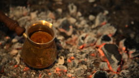 Traditional process boil Turkish coffee on coals. Boil Turkish coffee on coals. In this video: Coffee in a turk is cooked on coals. Added light to light the stock footage