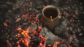 Traditional process boil Turkish coffee on coals. Boil Turkish coffee on coals. In this video: Coffee in a turk is cooked on coals. This is a traditional recipe stock video
