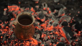 Traditional process boil Turkish coffee on coals. Boil Turkish coffee on coals. In this video: Coffee in a turk is cooked on sparkling coals. This is a stock video footage