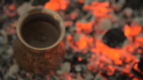 Traditional process boil Turkish coffee on coals. Boil Turkish coffee on coals. In this video: Coffee in a turk is cooked on sparkling coals. This is a stock footage