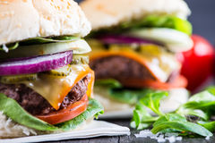 Traditional pub style burger  on wooden table Royalty Free Stock Photography