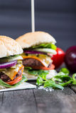 Traditional pub style burger  on wooden table Stock Images