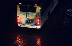 Traditional public bus of India running on a wet road. A beautiful traditional bus is running on a wet road at night isolated unique stock photograph Stock Photography