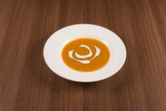 Simple pumpkin cream soup. Traditional pumpkin cream soup on a white background Royalty Free Stock Images