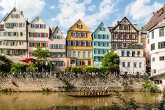 Traditional punt in front of the waterfront of. Tubingen, Germany - May 17,2015: A traditional punt is passing the beautiful waterfront of Tubingen (Tuebingen) Stock Images