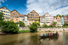Traditional punt in front of the waterfront of. Tubingen, Germany - May 17,2015: A traditional punt is passing the beautiful waterfront of Tubingen (Tuebingen) Royalty Free Stock Photo