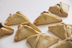 Traditional purim triangular pastry stuffed with figs. Photo of triangular pastry stuffed with figs, ears of Haman - Ozney Haman - hamantaschen, on a white Stock Photos