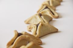 Traditional purim triangular pastry stuffed with figs. Photo of triangular pastry stuffed with figs, ears of Haman - Ozney Haman - hamantaschen, on a white Royalty Free Stock Photography