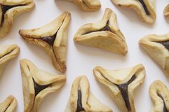 Traditional purim triangular pastry stuffed with figs. Photo of triangular pastry stuffed with figs, ears of Haman - Ozney Haman - hamantaschen, on a white Royalty Free Stock Images