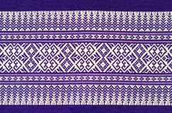 Traditional purple Thai fabric pattern as backgrou. Traditional hand-woven colorful batik cloth fabric in thai pattern Royalty Free Stock Photo