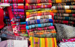 Traditional quechua textil. Indian quechua traditional  textil in the market shop in Peru and Bolivia. Red, yellow, blue, green, violet colour covers lie in a Royalty Free Stock Photo